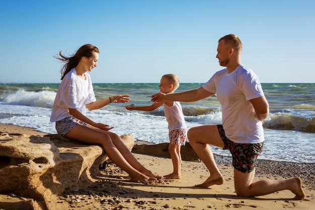Felice giovane famiglia sulla spiaggia in riva al mare, divertendosi. concetto di vacanza in famiglia