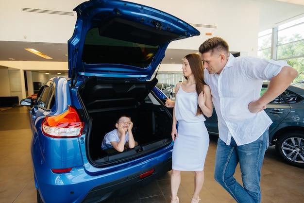 Una giovane famiglia felice presso il concessionario di automobili