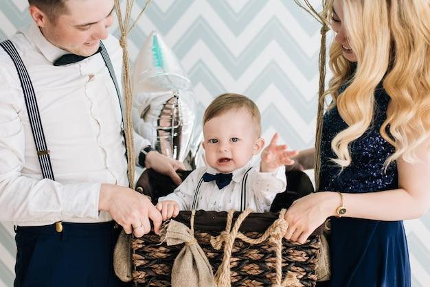 La giovane famiglia felice celebra il primo compleanno del bambino. il bambino ha 1 anno. il concetto di una festa per bambini con palloncini