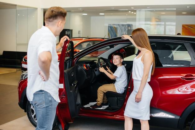 Felice giovane famiglia sceglie e acquista una nuova auto presso una concessionaria di automobili