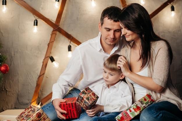 Felice giovane famiglia in decorazioni natalizie, mamma, papà e ragazzino vicino all'albero di natale con regali vicino