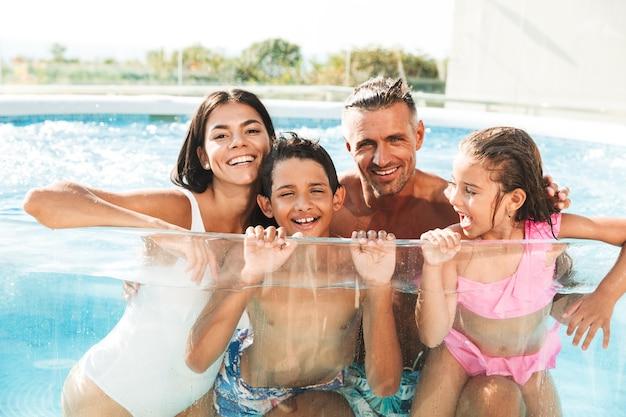 Felice giovane famiglia divertendosi all'interno di una piscina