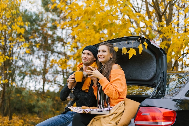 Una giovane famiglia felice si sta rilassando dopo una giornata trascorsa all'aperto nella foresta d'autunno.