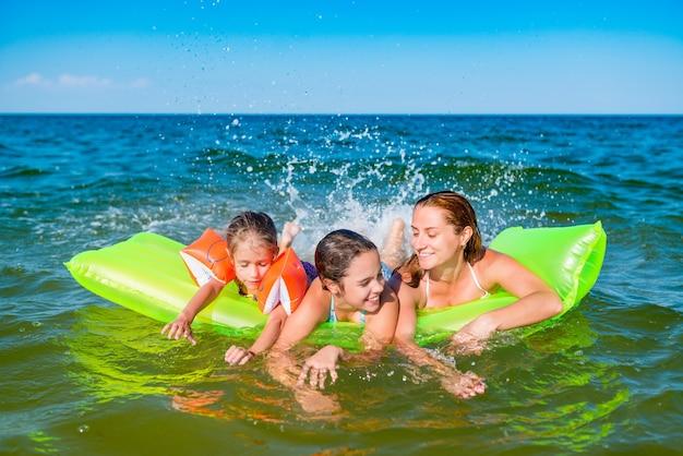 Felice giovane famiglia positiva mamma e due figlie piccole nuotano su un materasso ad aria giallo in mare in una soleggiata giornata estiva durante le vacanze