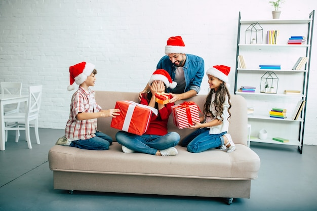 Giovane famiglia felice in cappelli rossi della santa che trascorrono tempo nel soggiorno