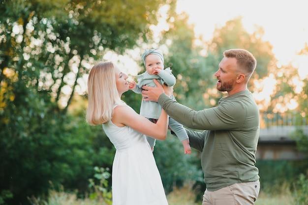 Felice giovane famiglia che trascorre del tempo insieme all'aperto nella natura verde.