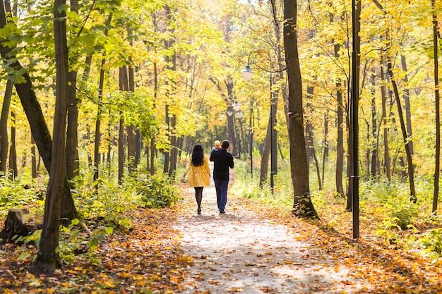Giovane famiglia felice che cammina per strada fuori nella natura autunnale