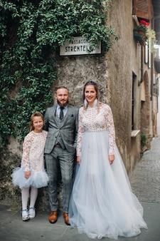 Una giovane famiglia felice cammina per il centro storico di sirmione in italia. famiglia alla moda in italia in una passeggiata.