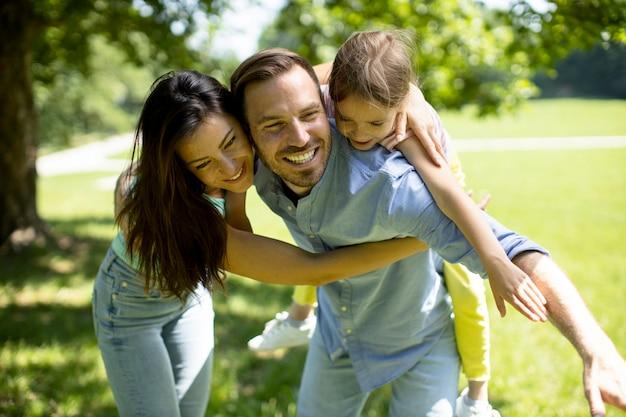 Felice giovane famiglia con una piccola figlia carina che si diverte nel parco in una giornata di sole