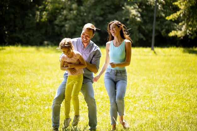Felice giovane famiglia con una piccola figlia carina che corre nel parco in una giornata di sole