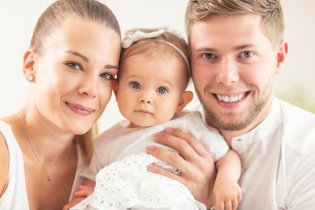 Felice giovane famiglia con madre, padre e figlia che sorridono tutti nella telecamera.