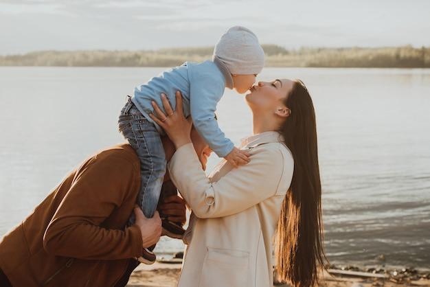 Felice giovane famiglia con il figlio sulla spiaggia in riva al fiume in estate