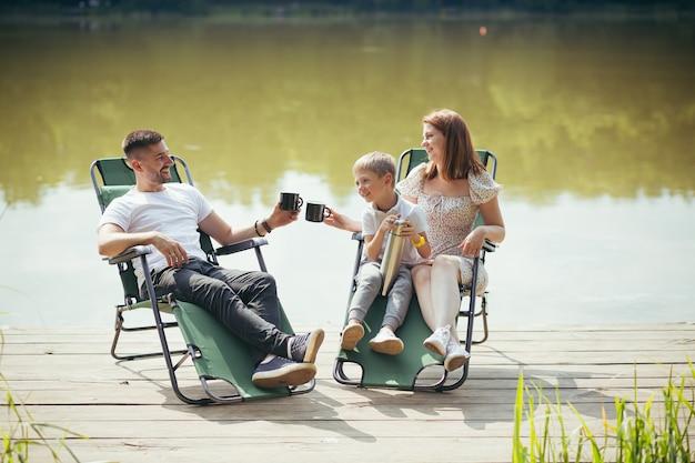 Felice giovane famiglia con bambini piccoli che riposano seduti su sedie pieghevoli da campeggio sul lago su un molo di legno all'aperto. trascorrere il tempo libero insieme nel pontone del campo con i bambini nella natura. foresta delle vacanze