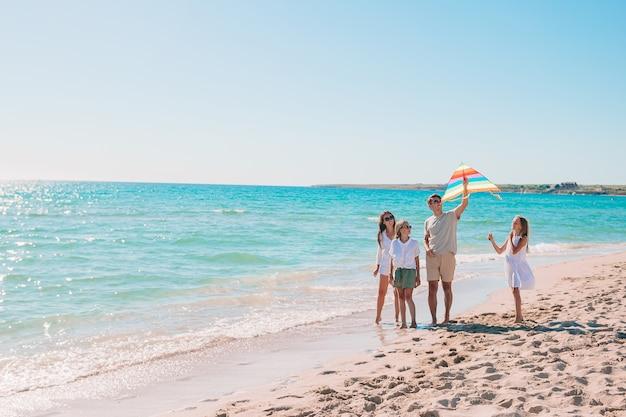Giovane famiglia felice con due bambini con volare un aquilone sulla spiaggia