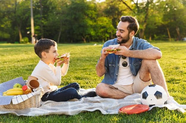 Felice giovane padre che fa un picnic con il figlioletto al parco, mangiando panini