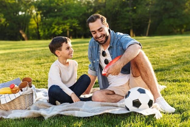 Felice giovane padre che fa un picnic con il figlioletto al parco, parlando