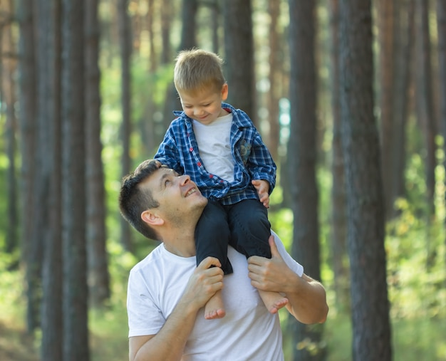 Giovane padre felice che ostacola nelle sue braccia piccolo bambino che lo mette su. festa del papà. figlio del bambino e del papà che gioca insieme all'aperto su una foresta di estate