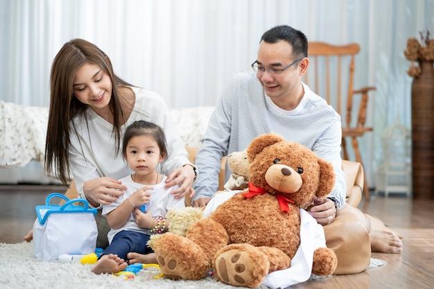 Felice giovane padre e madre e una piccola figlia che gioca con il giocattolo, seduto sul pavimento in soggiorno, famiglia, genitorialità e concetto di persone