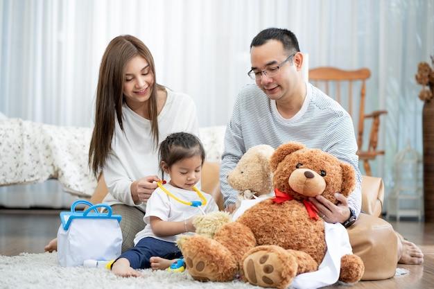 Felice giovane padre e madre e una piccola figlia che gioca con il giocattolo, seduta sul pavimento in soggiorno, famiglia, genitorialità e concetto di persone