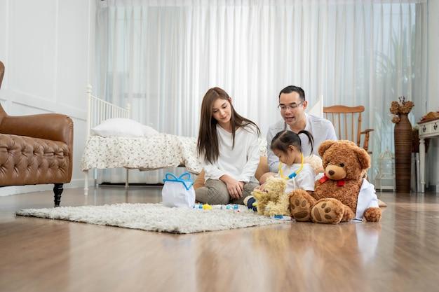 Felice giovane padre e madre e una piccola figlia che gioca con il giocattolo, seduto sul pavimento nel soggiorno, famiglia, genitorialità e concetto di persone