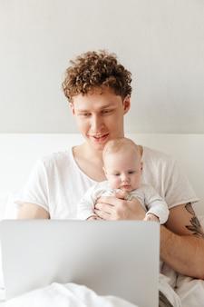 Felice giovane padre che gioca con il suo piccolo figlio mentre lavora su un computer portatile, sdraiato a letto
