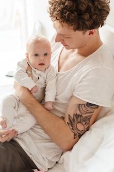 Felice giovane padre che gioca con il suo piccolo figlio piccolo mentre giace a letto a casa, abbracciando