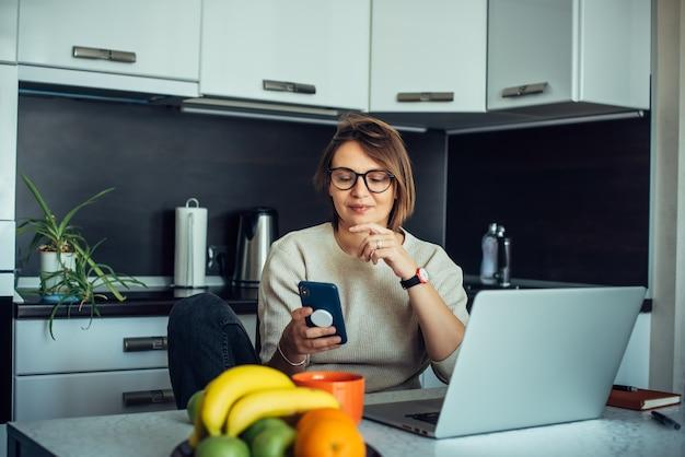 Felice giovane blogger femminile con gli occhiali in una cucina di casa con trasmissione in diretta di laptop. comunicazione con gli iscritti, lavoro a distanza, distanza sociale.