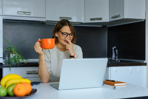 Felice giovane blogger femminile con gli occhiali in una cucina di casa con la trasmissione di laptop in diretta. comunicazione con gli iscritti, lavoro a distanza, distanza sociale.