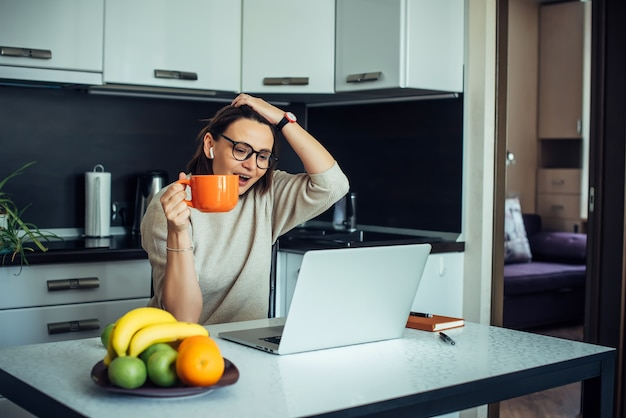 Felice giovane blogger femminile con gli occhiali nella cucina di casa con la trasmissione in diretta del laptop
