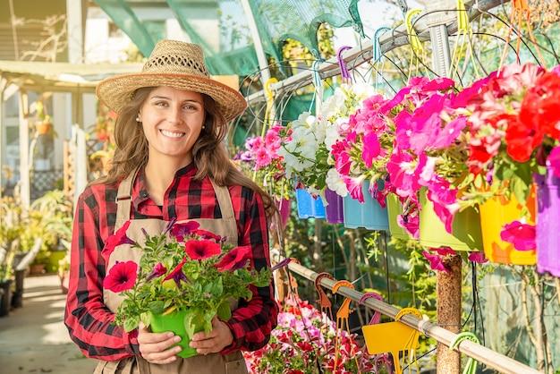 Felice giovane femmina sorridente fioraio che lavora in una serra nel centro giardino con fiori rossi
