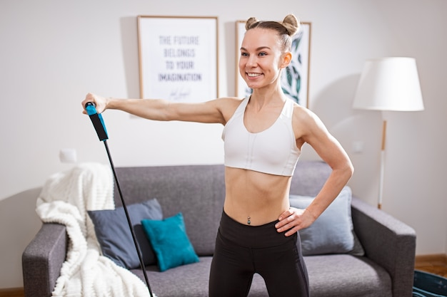 Felice giovane donna in abiti sportivi tenendo la mano sulla vita e sorridente mentre si allunga la corda elastica durante l'allenamento fitness a casa