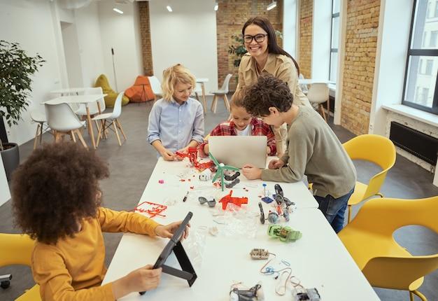 Felice giovane insegnante con gli occhiali che sorride alla telecamera mentre aiuta i bambini a costruire giocattoli robotici