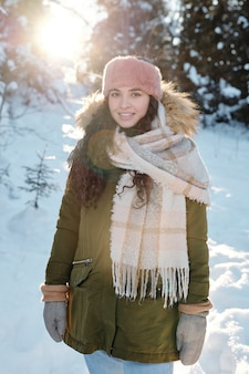 Felice giovane donna in abbigliamento invernale in piedi nella foresta