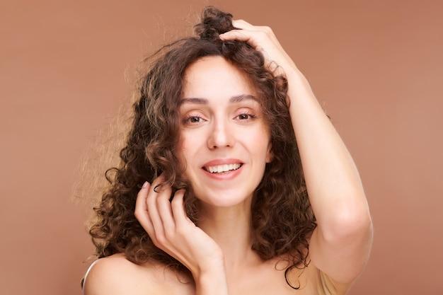 Felice giovane femmina con sorriso a trentadue denti, pelle sana e lussuosi capelli scuri ondulati guardando la parte anteriore