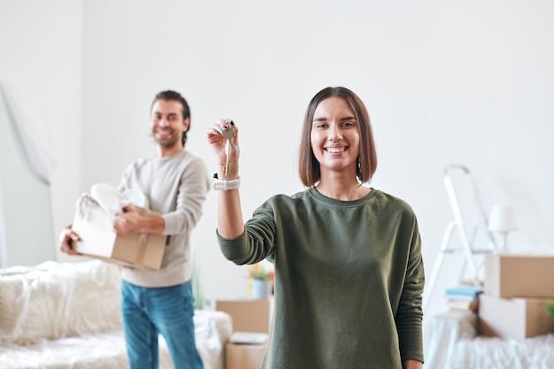 Felice giovane donna con un sorriso a trentadue denti che ti mostra la chiave dal nuovo appartamento o casa
