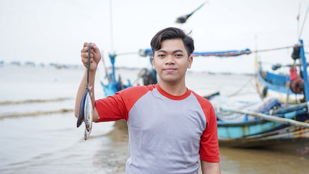 Felice giovane pescatore sulla spiaggia tenendo il suo pescato e spettacoli davanti alla sua barca