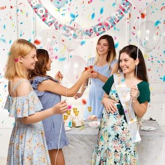 Giovani amici felici che festeggiano insieme durante il genere rivelano la festa, su palloncini e sfondo di coriandoli.