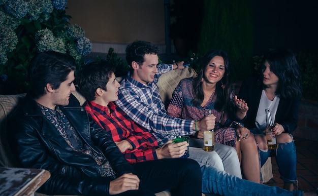 Giovani amici felici che bevono e si divertono in una festa all'aperto. concetto di amicizia e celebrazioni.