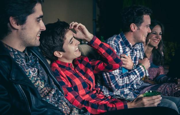 Giovani amici felici che bevono e ridono in una festa all'aperto. concetto di amicizia e celebrazioni.