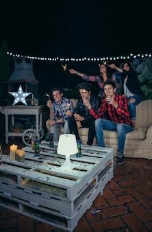 Giovani amici felici che tengono le stelle filanti e si divertono in una festa notturna all'aperto. concetto di amicizia e celebrazioni.
