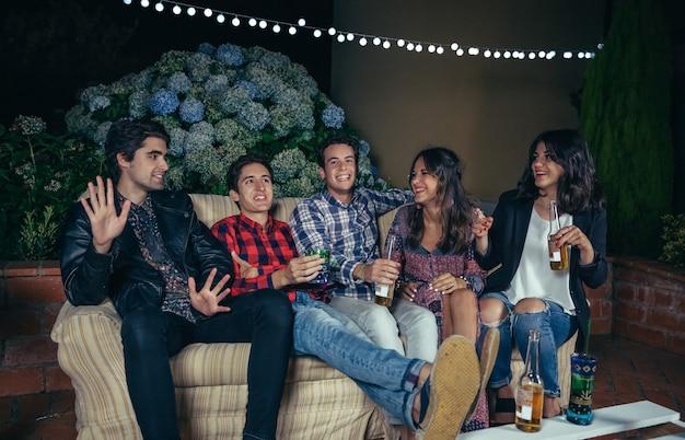 Giovani amici felici che ridono e si divertono in una festa all'aperto. concetto di amicizia e celebrazioni.