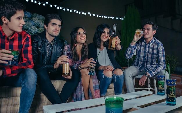 Giovani amici felici che ridono e parlano mentre la donna mostra la birra in una festa all'aperto. concetto di amicizia e celebrazioni.