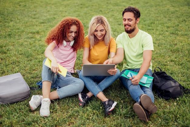 Giovani amici felici che sorridono e che passano in rassegna laptop sull'erba