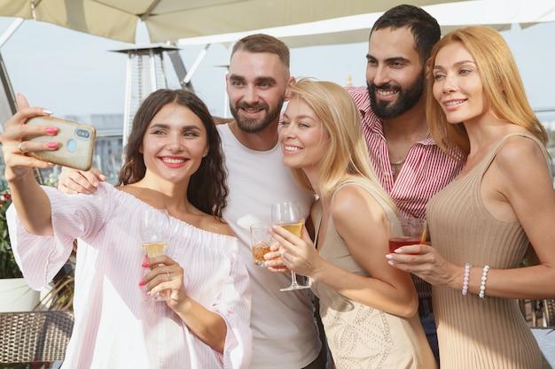 Giovani amici felici che prendono selfie durante la festa sul tetto