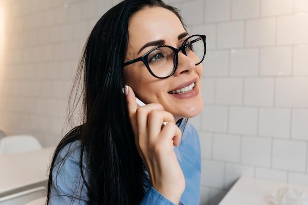 Ragazza felice in camicia blu e occhiali che parla al telefono