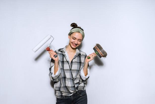 Felice giovane costruttore di ragazze che tiene un pennello e un rullo per dipingere le pareti
