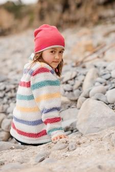 Ragazza felice in cappotto colorato, cappello rosa, pantaloni neri seduto e giocando in riva al mare