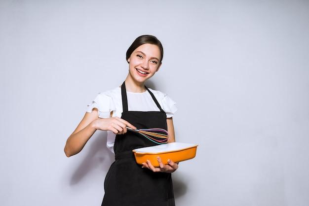 Cuoco felice della ragazza in un grembiule nero che prepara una torta deliziosa, sorridente