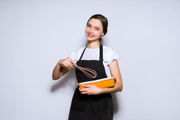 Cuoco felice della ragazza in un grembiule nero che prepara una torta deliziosa