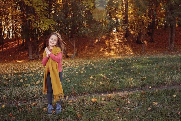 Ragazza felice che gode della giornata di sole nella foresta di autunno